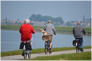 Elderly riding bikes along a lakeside