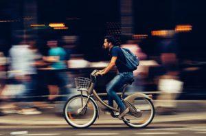 Biker rides past blurred cafe background