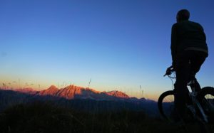 Biker looks at sunset on mountains in the distance