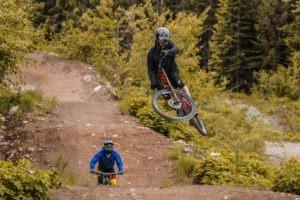 Biker jumps a dirt ramp