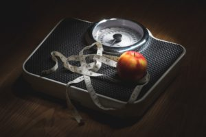 Electric Bike Health Benefits: Measuring tape and apple on scales