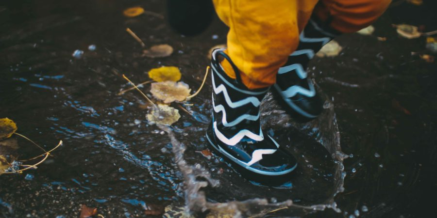 Best Waterproof Cycling Pants: A kid in gumboots splashes in a puddle