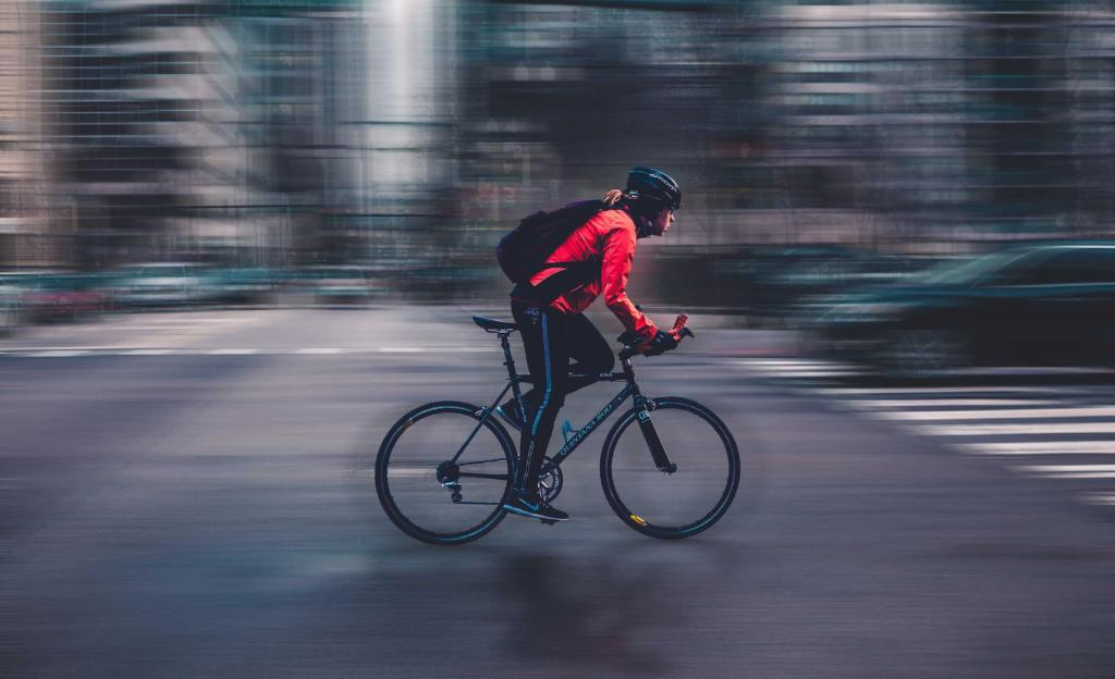 Blurry image of man cycling on road
