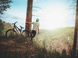 Man Swings Off Tree With Bike Beside Him