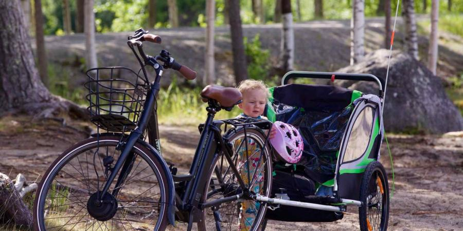 Child standing beside bike with small trailer